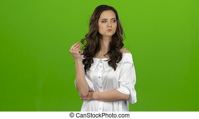 Girl worries bites her lip and nervously corrects her hair. Green screen