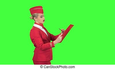 Girl writes a pen with a special folder, she is a stewardess smiling and benevolent. Green screen. Side view