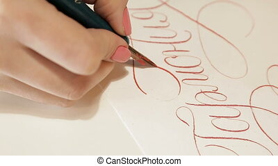 Girl writes calligraphy. Beautiful letters on paper.