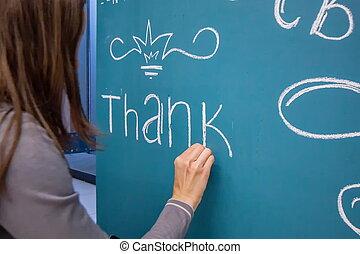 Girl writes chalk congratulation on the blue board