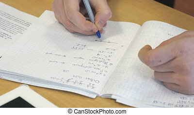 Girl writes in a school mathematics notebook