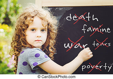Girl writes in chalk on a blackboard. Peace concept. Toning photo.