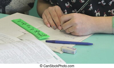 Girl writes in copybook at the lesson - Girl sitting at the...