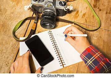 girl writes in notebook with cell phone and old camera