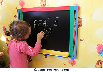 girl writes on a blackboard a word the peace