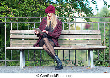 Girl writes on a tablet in the bench