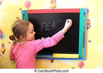 girl writes on blackboard word the peace