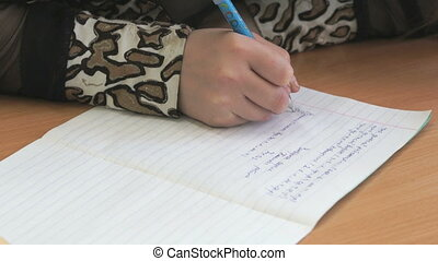 Girl writes the text in a copybook using a pen - The girl...