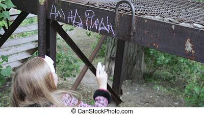 Girl writes with chalk on the iron - On an iron surface a...