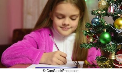 Girl writing a letter to Santa Claus, the focus is on the fur-tree in front of her