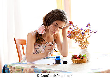 girl writing at table by pen and ink indoor in summer day with strawberries