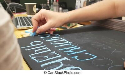 Girl writing chalk on a blackboard