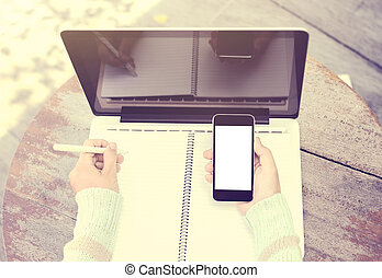 girl writing in a notebook with a cell phone and a laptop, vintage color effect