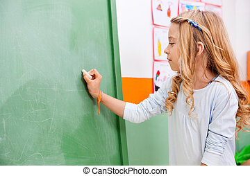 Girl Writing On Green Chalkboard In Kindergarten