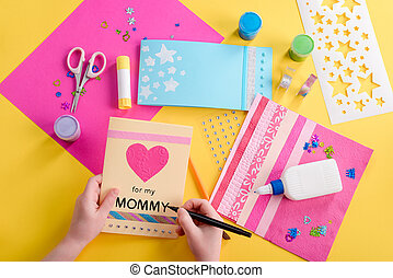 Girl writing on greeting card. Colored paper, decorative elements and tools