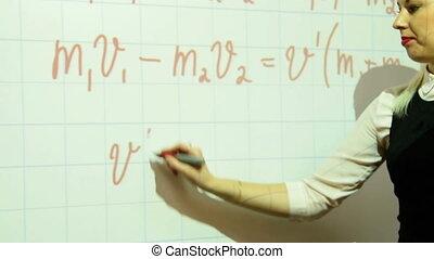 Girl writing physics formula on interactive whiteboard