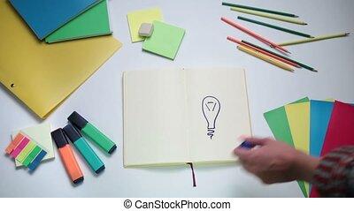 Girl writing word idea on notepad above lightbulb