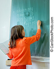 A little girl writting and drawing on the green board