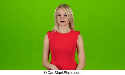 Girl yawns covering her mouth with hand. Green screen studio
