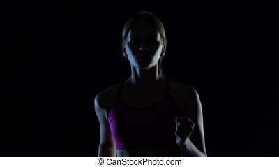Girl young in pink top runs on a black background. Silhouette. Slow motion. Close up