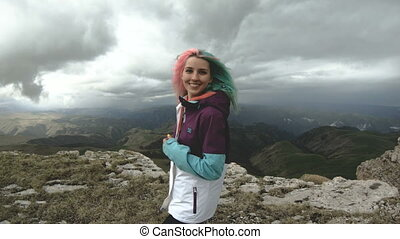 Girl young woman dances on the edge of a cliff of a plateau...