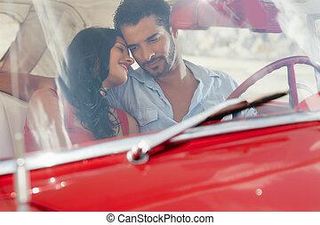 girlfriend and boyfriend flirting in red old car