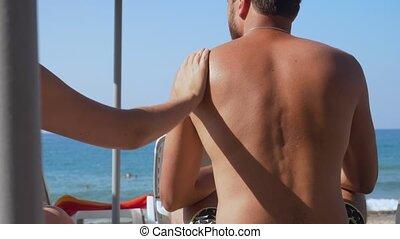 Girlfriend applying cream to her boyfriend on the beach.