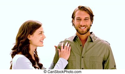 Girlfriend kissing boyfriend on the cheek on white background in slow motion