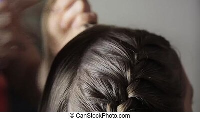 girlfriend plaiting pigtail for young brunette woman