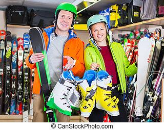 girlfriend with man are choosing ski