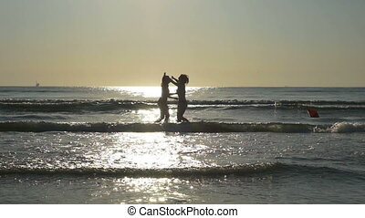 Girlfriends hugging on the shore of a sandy beach with their feet in the water in slow motion