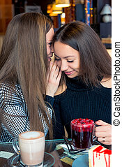 Girlfriends in a cafe gossip and drink coffee