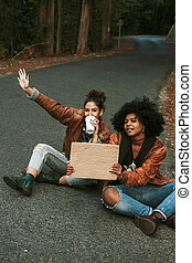 girlfriends on the road hitchhiking with sign