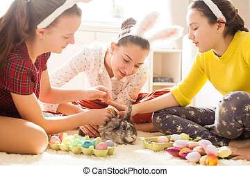 Girlfriends playing with  rabbit