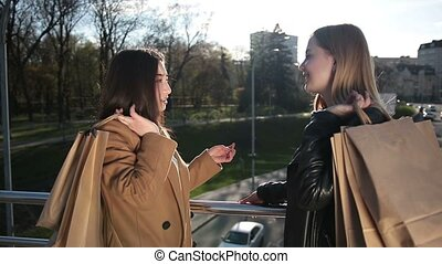 Girlfriends sharing impressions after shopping