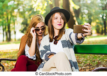 Girlfriends taking a selfie on the bench park