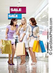 Girlfriends - Three joyful girlfriends in shop with a credit...
