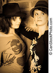 Girlfriends - Two girls standing at a wall. One looks to the...