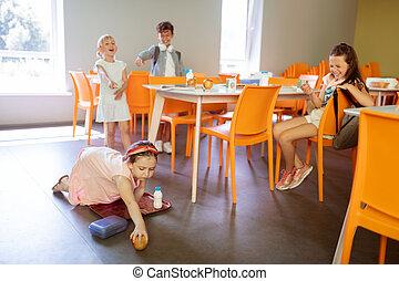 Girls and boy bullying poor little girl dropping apple on floor