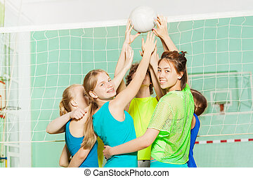 Girls and boys playing volleyball in gymnasium
