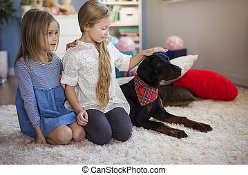 Girls and dog sitting in a row
