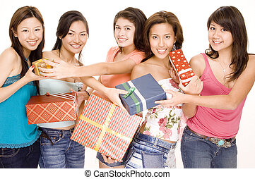 Five pretty asian women swap gifts and presents