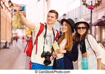 Girls and guy taking selfies with mobile phone