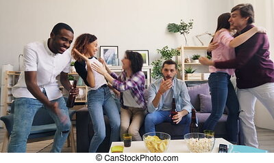 Girls and guys are happy after watching sports game on TV at home together