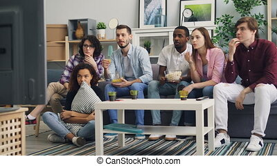 Girls and guys are chatting having fun at home then watching horrible news on TV discussing tragedy looking at screen shocked and upset. People and emotions concept.