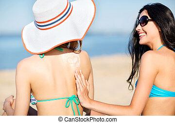 girls applying sun cream on the beach