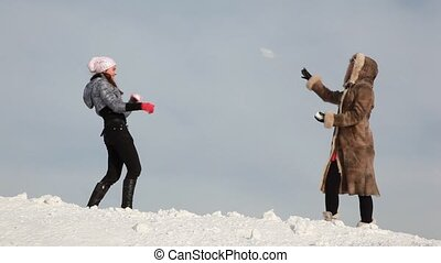 Girls are playing snowballs on slope with snow