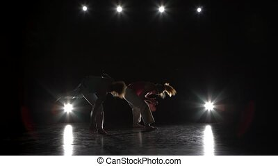 Girls are practicing capoeira in darkness against spotlight....