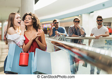 Girls are shopping at the mall. Sale in black Friday. Girls are shopping on a black Friday.