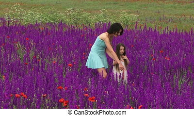 Girls are walking among the flowers